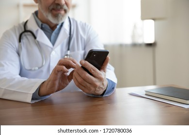 Senior professional male doctor holding mobile phone modern technology apps sitting at desk. Older physician using smartphone gadget tech for telemedicine remote online services concept. Close up view