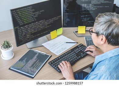 Senior Professional programmer working at developing programming and website working in a software develop company office, writing codes and typing data code.