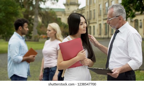 Senior professor talking to Asian student, discussing science project on campus
