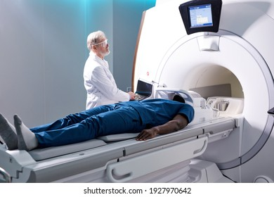 Senior Radiologist Controls MRI or CT or PET Scan with Male Patient Undergoing Procedure. High-Tech Modern Medical Equipment. Friendly Doctor Working With Patient