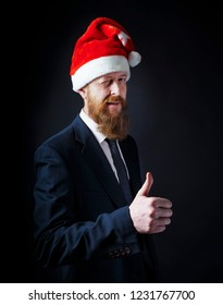 Senior red bearded Businessman winks and showing thumbs up in santa hat on black background.