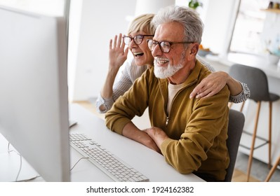 Senior retired couple learn about computer and online support.