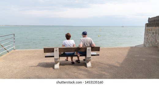 Senior retired couple looking sea sit on bench on vendee beach France in web banner template