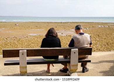 Senior retired couple looking sea sit on bench at Saint Vincent sur Jard in vendée beach France
