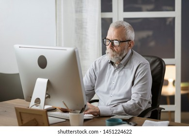 Senior retired man sitting ad desk and working with a computer, elderly and technology concept