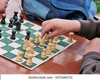 Senior retired men playing chess in the park. elderly male hand moves a white knight on the chess board.
