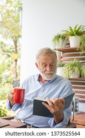 Senior retirement man happy reading book at home