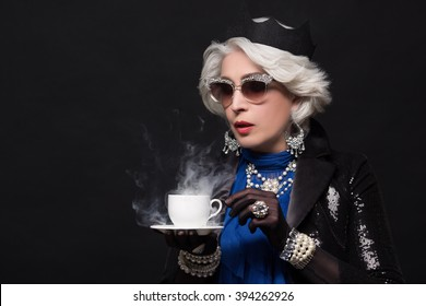 Senior rich woman having a cup in Queen Elizabeth. Beautiful old lady in expensive and fashionable clothes isolated over black background.