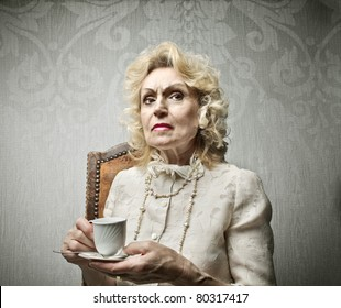 Senior rich woman having a cup of tea