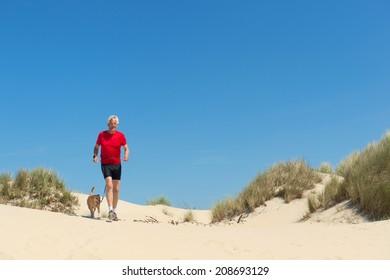 Senior runner with dog in nature dunes
