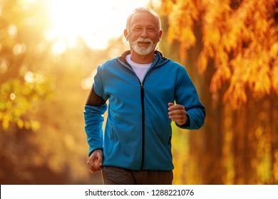 Senior runner doing stretching in autumn park.