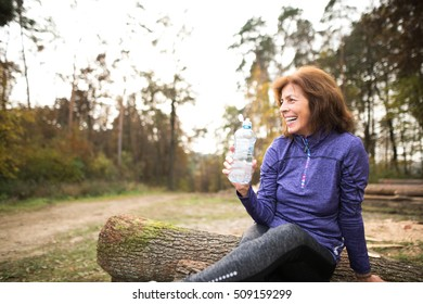 Senior runner sitting on wooden logs, resting, drinking water.