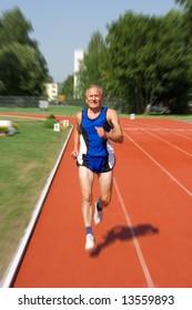 Senior runner in a stadium. Motion effect