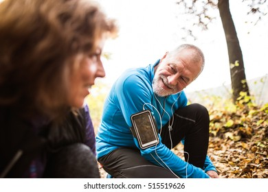 Senior runners in nature, tying shoelaces. Man with smartphone.