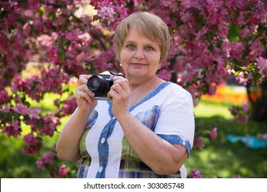 Senior Russian woman taking puctures in park