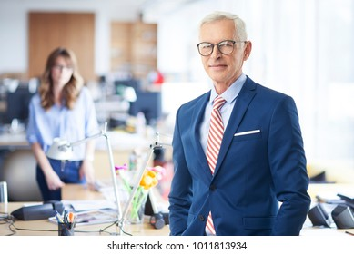 A senior sales director businessman looking at camera and smiling while standing at the office.