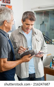 Senior salesman holding electronic reader while man paying through smartphone in hardware store