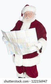 Senior Santa Claus looking in to road map isolated over white background