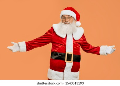 Senior Santa Claus in red traditional costume and eyeglasses looks very surprised with wide open arms isolated on orange background. Concept of winter holidays
