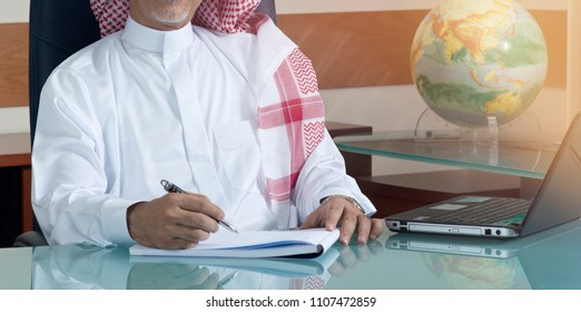 Senior Saudi Businessman Hand Writing At His Desk with Laptop