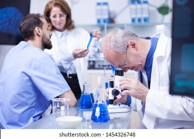 Senior scientist doing testing under the microscope in a modern laboratory. Team of scientist working in the background.