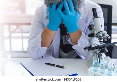 Senior scientists fail with scientific research on the desk in the laboratory and researching the chemical that had fallen badly.