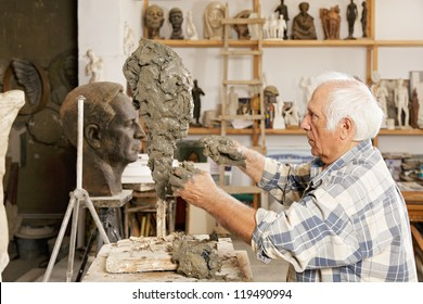 Senior sculptor making sculpture putting clay on wire skeleton sideview