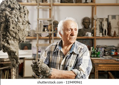 Senior sculptor standing in workshop against sculpture and kneads clay