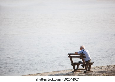 Senior sitting on a bench and looking away. Senior is sitting alone on the bench looking at