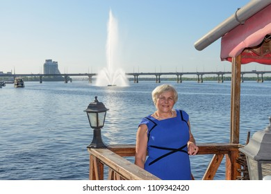Senior smiling blonde woman is posing on background of Dnieper river with floating fountain and bridge in light of sunset in Dnepr town, former Dnepropetrovsk in Ukraine.