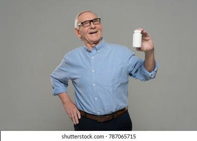 Senior smiling man holds white bottle of pills isolated on gray background