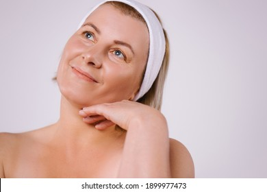 Senior smiling woman with clean and moisturized skin after home procedures looks to the side against a gray background with side space.