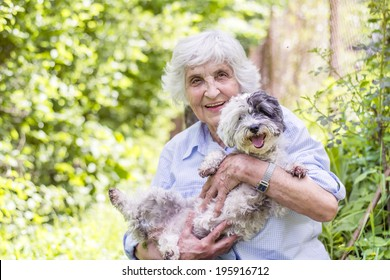 Senior smiling woman hugging her dog in the mountain