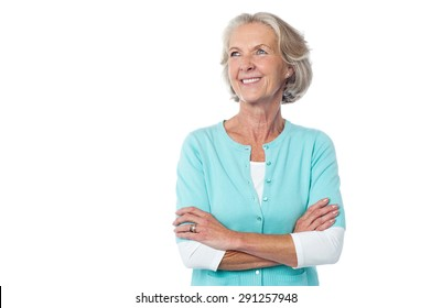 Senior smiling woman looking up with arms crossed