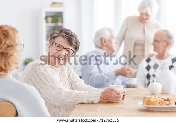 Senior Social Life Konzept, Gruppe der Senioren im Alter zu Hause zu sprechen und gute Zeit zusammen zu haben, konzentrieren sich auf eine ältere Dame, die unter Kamera lächelt