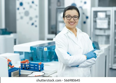 Senior specialist. Cheerful elderly female scientist smiling happily with her arms crossed posing at her lab colleagues on the background teamwork profession professor guidance people job copyspace
