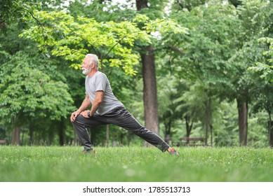 Senior sportsman doing stretching exercise at park