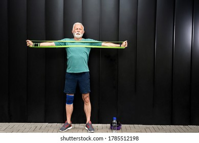 Senior sportsman exercising with resistance band