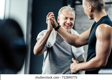 senior sportsman giving highfive to trainer in sport center