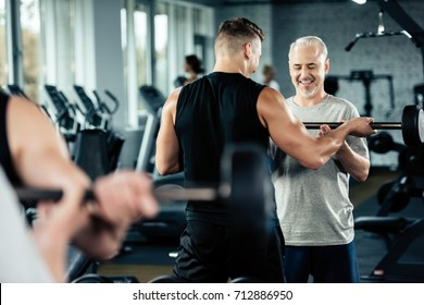senior sportsman training with barbell and young trainer in gym