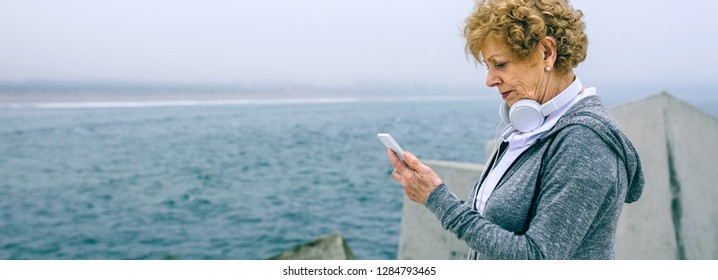 Senior sportswoman looking at her smartphone by sea pier