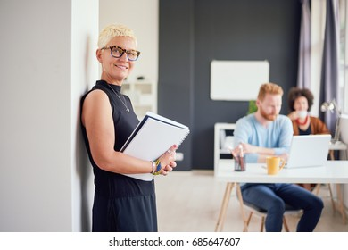 Senior standing in modern office against the wall and holding notebook
