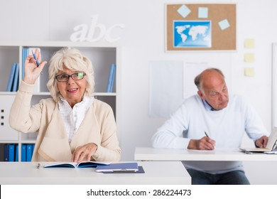 Senior student sitting at the desk and raising hand