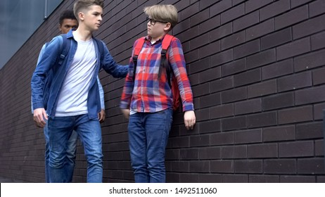 Senior students pushing and punching boy in school backyard, bullying of weak