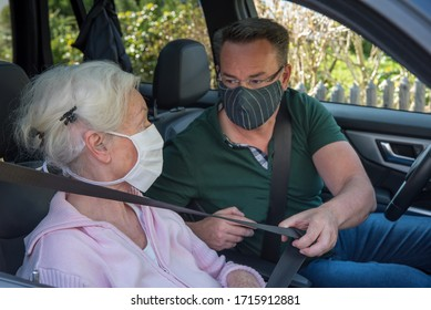 Senior and sun with face masks in the car