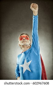 senior superhero man in blue costume red cloak and mask old portrait on textured background