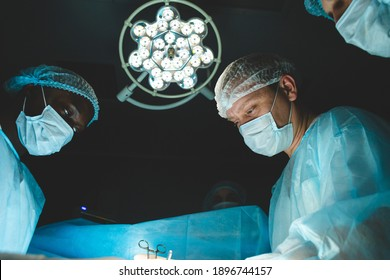 The senior surgeon in the operating room, where the patient is waiting for him, and he begins the operation. Real Modern Hospital with Authentic Equipment.