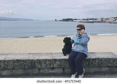 senior talking on the phone with dog