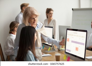 Senior team leader teaching new employee explains planning work schedule in office with planner calendar, aged executive helps young worker using corporate applications on computer, mentoring concept