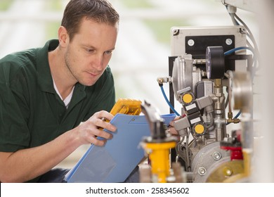 Senior technician repairing agriculture machinery in a greenhouse